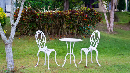 Outdoor white table and chairs  in a garden on green lawn Stock Photo