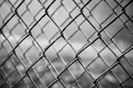 close-up of rusty steel mesh fence, very shallow depth of field. Black & White.