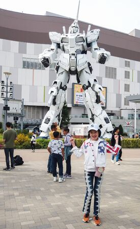 TOKYO, JAPAN - MAY 10 : Unidentified tourist take picture with Unicorn Gundam robot statue in front of the Diver City plaza in Odaiba Shopping mall in Japan on May 10, 2019 in Tokyo, Japan