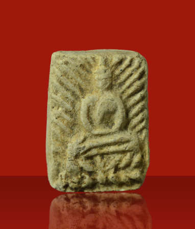 Small Buddha image or Amulet of thailand on red background Standard-Bild