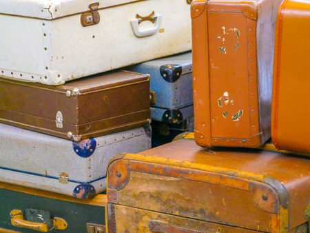 A collection of stacked old suitcases at an airport Stock Photo