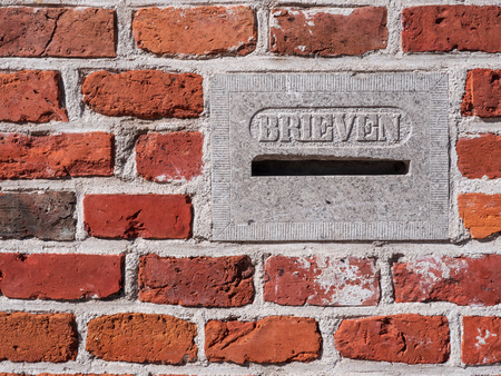 Old stone letterbox in brick wall, with the Dutch text letters. Photographed in the city of Groningen.