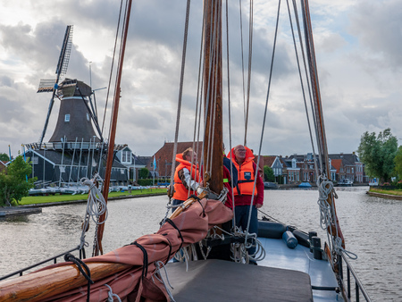 Woudsend, The Netherlands - june 21 2018: sailing with a skutsje through the Frisian water sport village Woudsend. With the sawmill in the background. The ship Aleida Hendrika is a ferry connection between Heeg and Balk. Editöryel