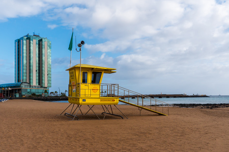 Arrecife, Spain - january 18 2018: Viewpoint of a lifeguard on an empty beach in Lanzarote, with a large hotel in the background. Editöryel