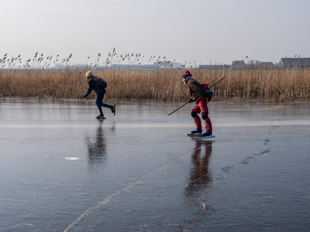 Woudsend, The Netherlands - march 3 2018: Ice skating during a cold but sunny winter day on natural ice in Friesland, in the north of the country. Typically Dutch.