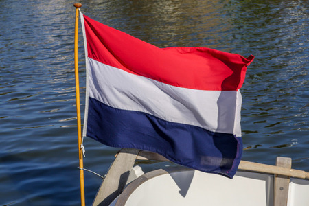 The Dutch flag waves proudly in the wind on the back of a motor sloop in the Dutch province of Friesland