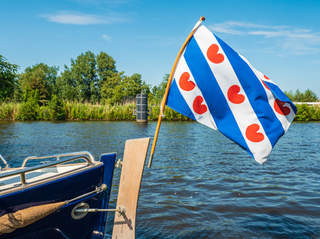 The Frisian flag waves proudly in the wind on the back of a motor sloop in the Dutch province of Friesland 免版税图像