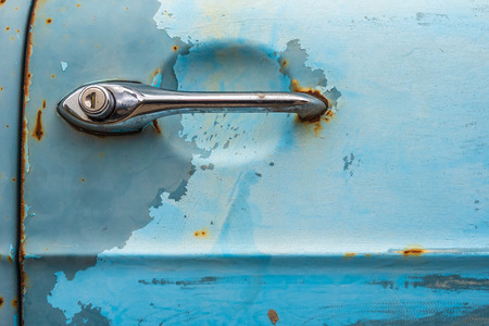 Detail photo of a blue and rusty car door with a chrome door handle. An old-timer pickup truck.
