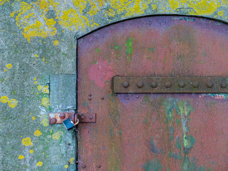 Old weathered and rusty steel door with padlock in monumental bunker, where the algae grow in the concrete.