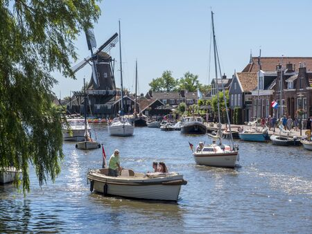 Woudsend, The Netherlands - June 30 2018: On a summer day, many water sports enthusiasts pass the tourist-oriented village in Friesland with their sloop, sailing boat or motorboat. 写真素材 - 141310561
