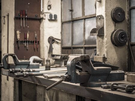 Old workshop with a workbench with a vise and many types of tools, both on the work table and on the wall.
