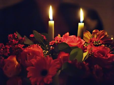 arrangment: Two candles lighting up an arrangment of flowers