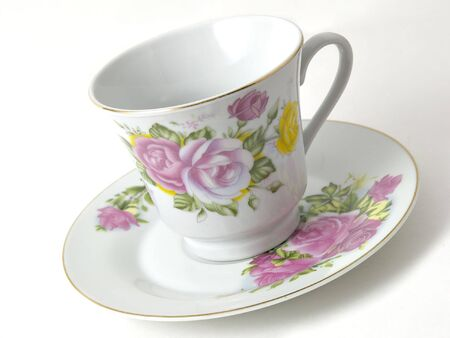 tilted: Tilted fancy coffee cup and saucer on a white background Stock Photo