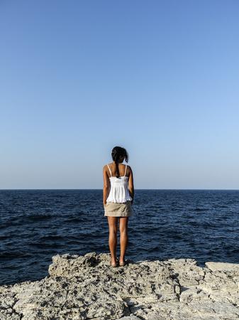 Schönes Mädchen, das den Ozean durch die Klippe betrachtet Standard-Bild