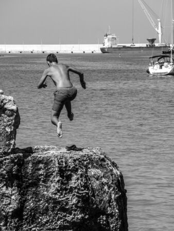 Young boy jumping from the cliff