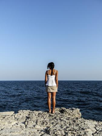 Schönes Mädchen, das den Ozean durch die Klippe betrachtet