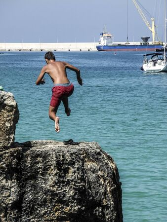 unafraid: Young boy jumping from the cliff
