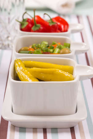 Chili sweet red and pickled green peppers with colorful salad, in food trays on diner table