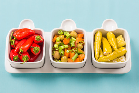 Chili sweet red and pickled green peppers with colorful salad, in food trays on blue background