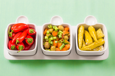 Chili sweet red and pickled green peppers with colorful salad, in food trays on a green background