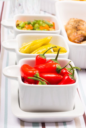 sallad: Chili sweet red and pickled green peppers with colorful salad, in food trays on diner table