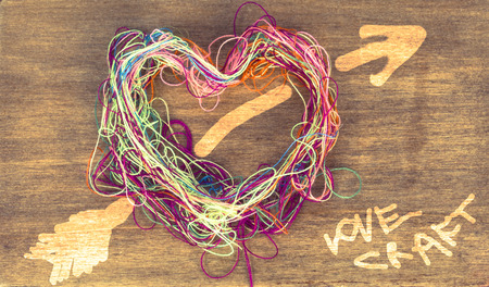 love craft multicolor thread heart on the wooden background photo