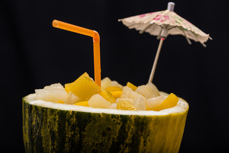 Fresh cocktail with fresh fruits straw and little umbrella in watermelon on black background photo
