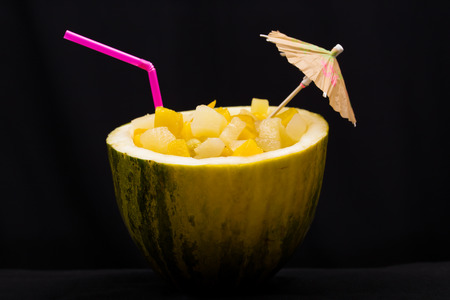 umbrela: Fresh cocktail with fresh fruits straw and little umbrella in watermelon on black background