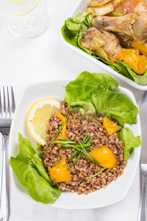 buckwheat and chicken with yellow pepper and lettuce on diner table in food tray photo