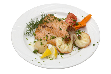gilled: Grilled salmon and shrimps with tomato and lemon on plate Stock Photo