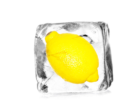 lemon, citron in a ice cube isolated with white background photo