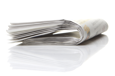 several newspapers, journals stacked on white background photo