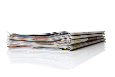 commonplace: several newspapers, journals stacked on white background
