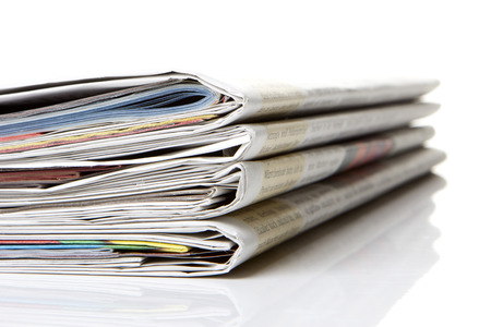 gazette: several newspapers, journals stacked on white background
