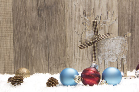 christmas decoration with wood background, snow, elk, christmas baubles gold, blue and red and pine cones  photo