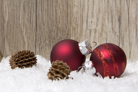 christmas decoration with wooden background, snow, christmas baubles red and pine cones  photo