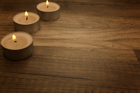 several tea lights with wooden background photo