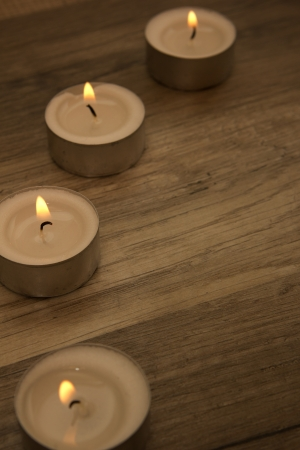 several tealights with wooden background photo