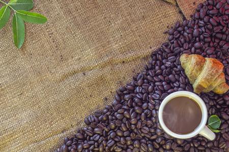 Tazza di caffè e cornetto su fagioli e sacco Archivio Fotografico - 90280606