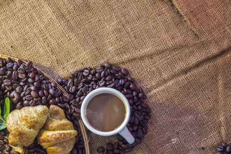 Coffee cup and Croissant on beans and sack