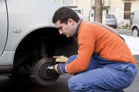 mechanic checking worn car brake Stock Photo - 12897481