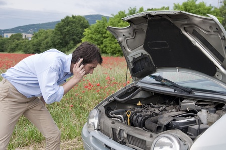 young man calling the car service after a vehicle breakdown