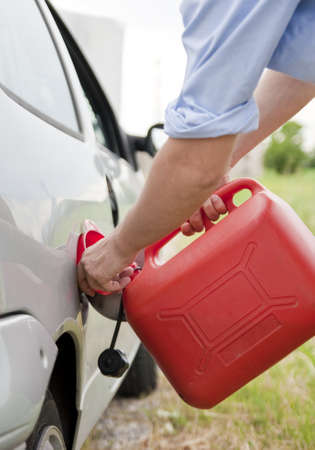 man refilling his car with funnel and red tank fuel Stock Photo - 10811403
