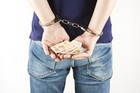 kriminellen Gefangenen mit Handschellen und Rechnungen in seinen Händen