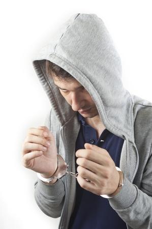 sweatshirt: junger Mann mit Handschellen isoliert auf wei�em Hintergrund festgenommen