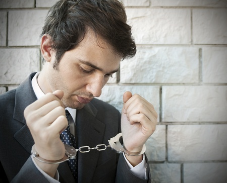 arrested criminal: portrait of a manager with handcuffs Stock Photo