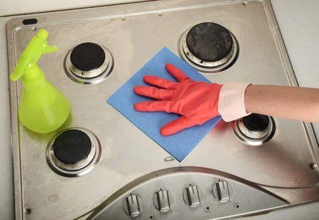 sponge cleaning a dirty inox gas cooker Stock Photo
