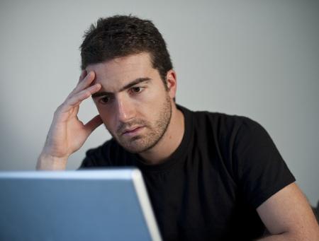 smutny mężczyzna: smutny czÅ'owiek reaing zÅ'e wieÅ›ci na swoim laptopie
