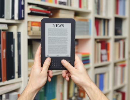 the reader: hands holding a ebook reading device and books on the background