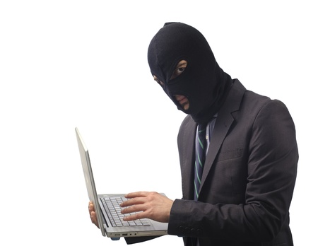 data theft: masked man hacker stealing data from a laptop